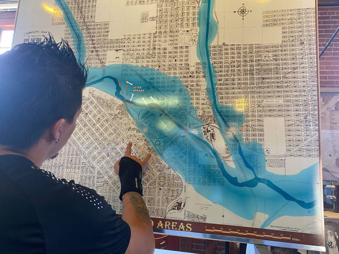 Mohammad Curtis, co-director of the Pueblo Heritage Museum, shows where the river was moved to on a map of the 1921 flooding. Photo captured May 25, 2021.