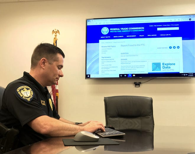 Capt. Adam Moore of the Delaware Police Department uses a wall-mounted computer screen to open a U.S. Federal Trade Commission webpage, where victims can report fraud, scams and identity theft.