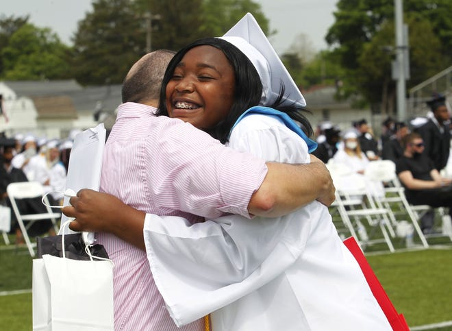 Whitehall-Yearling High School faculty member Chad Thatcher hugs graduating senior Cierra Battiste during commencement May 22 at the high school stadium.