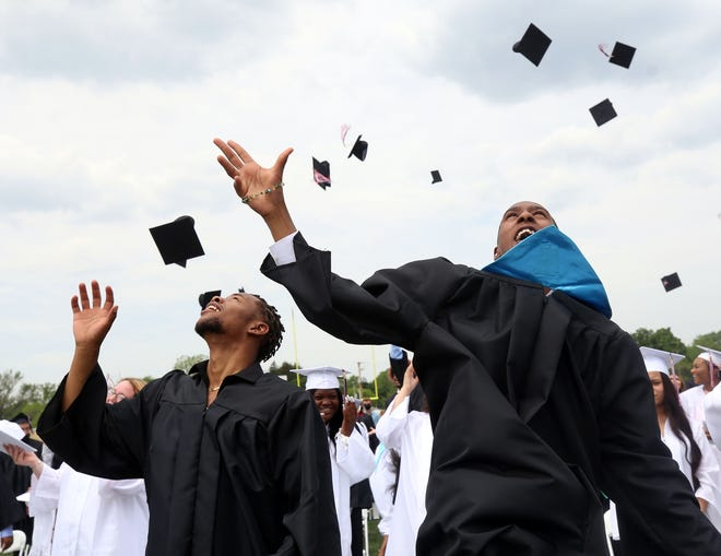 Jay'Saun Sna'Ron Brown (left), Dazery Teddy Brown and the rest of the  Whitehall-Yearling High School class of 2021 throw their caps into the air following commencement exercises May 22 at the high school stadium.  This was the first time since 1979 that graduation ceremonies were held at the school building.