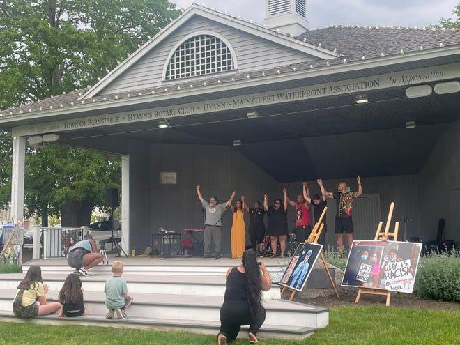 Performers at last Sunday's 'A-Way with Words' take a bow on the Hyannis Village Green in honor of the late George Floyd of Minneapolis on the first anniversary of his murder, which triggered a global racial reckoning. From left: Mwalim, Amanda Shea, Tamora Israel, Mea Johnson, Shadow Master, Chuck V, and KAIROS. Organizer Rachael Devaney of Onset takes their photo in the foreground.