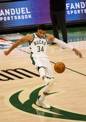 Milwaukee Bucks forward Giannis Antetokounmpo playfully kicks the ball after getting fouled by the Miami Heat during the second half of Game 2 of their NBA basketball first-round playoff series Monday, May 24, 2021, in Milwaukee.