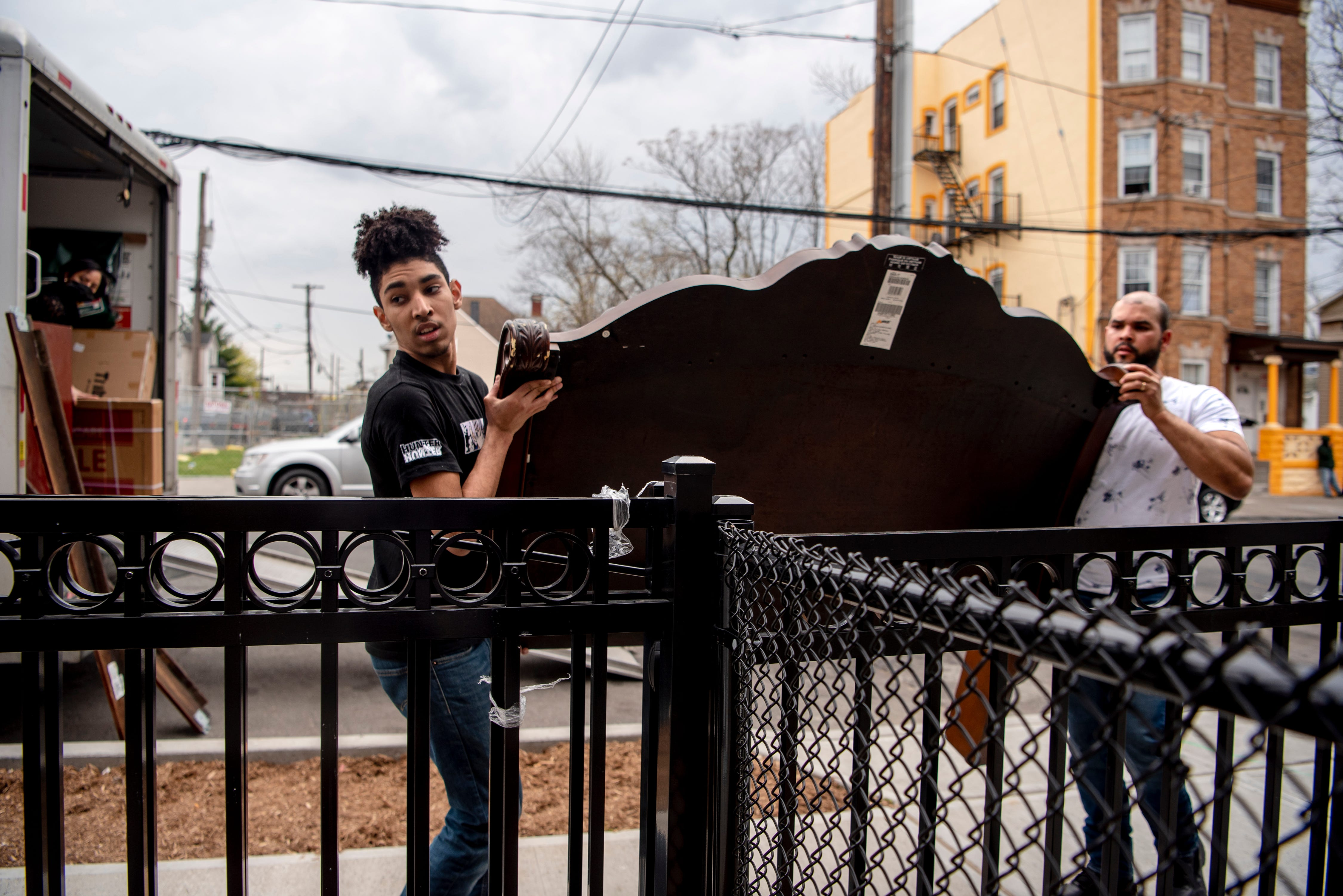 Carlos De Los Santos, 17 and his stepfather Ronny Brito unpack the moving van outside of the family's new Habitat for Humanity home on Hamilton Ave. in Paterson on April 9, 2021.