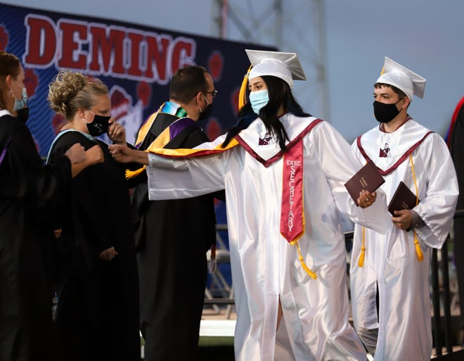 Deming High graduate Jenae Jasso reaches out to give a fist pound to administrators after receiving her diploma.