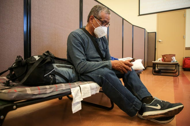 Jairo Martinez sits on a cot inside the Galilee Center in Mecca, Calif., after fleeing Venezuela to seek asylum in the United States on Monday, May 24, 2021.