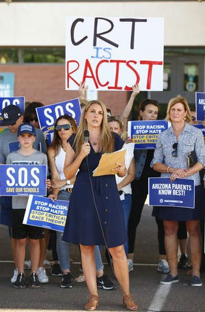 Amy Carney speaks on behalf of parents during a protest against critical race theory being taught at Scottsdale Unified School District before a digital school board meeting at Coronado High School in Scottsdale on May 24, 2021.