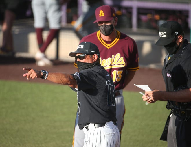 Grand Canyon University baseball coach Andy Stankiewicz points out the ground rules to Arizona State University coach Tracy Smith before playing at GCU Ballpark in Phoenix April 21, 2021.
