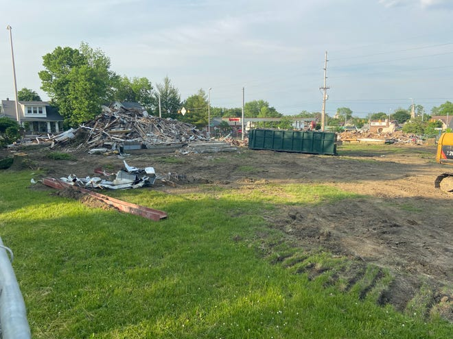 Rubble piles remain Monday, May 24, 2021, where three houses formerly stood along National Road West.