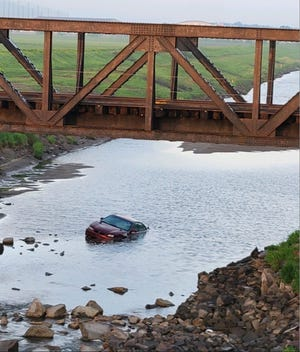 A red car is seen in the Big Sioux River north of town along the bike trails Tuesday morning. Sioux Falls Fire Rescue officials said it's there for training purposes.