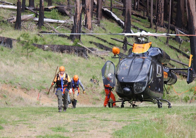 Searchers exit helicopter after locating Harry Burleigh.
