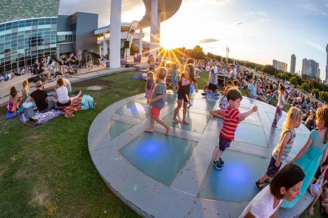 Children play at the Long Center during an Austin Symphony Orchestra concert in the park. Due to the pandemic, ASO canceled last year's events, but will bring back the free concerts almost every Sunday this summer.