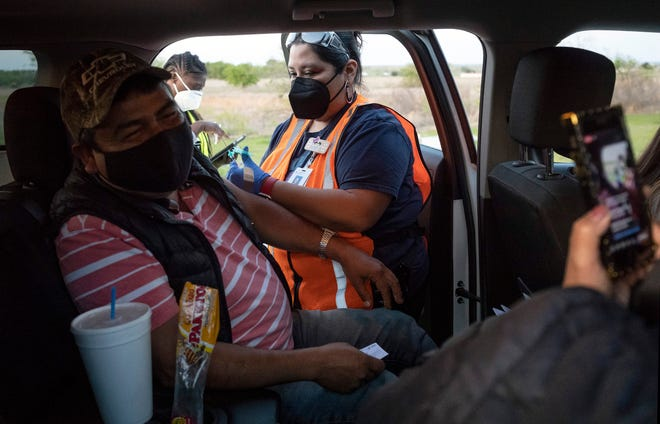 Volunteer Adriana Castro gives David Hernandez his first dose of the COVID-19  vaccine during a drive-thru vaccine center held at the Manor High School stadium, on April 1. [AMERICAN-STATESMAN/FILE]