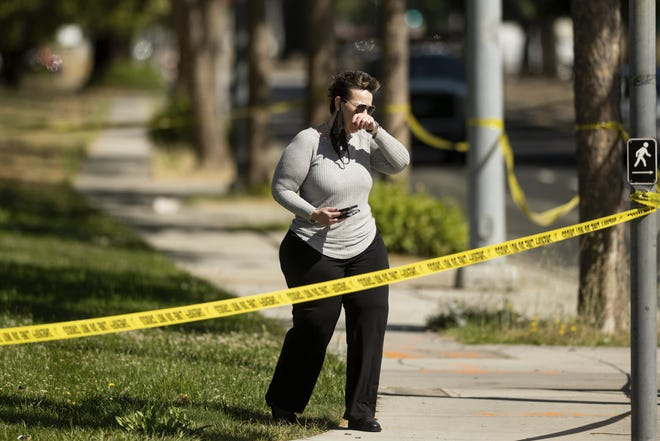 A woman leaves the scene of a shooting at a Santa Clara Valley Transportation Authority (VTA) facility on Wednesday, May 26, 2021, in San Jose, Calif. Santa Clara County sheriff's spokesman said the railyard shooting left multiple people, including the shooter, dead.