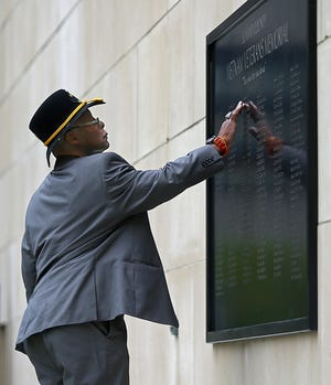 Johnnie Downs, an Army veteran, runs his fingers over the name of high school friend William Stuart Glenn, who was killed in the Vietnam War, after Wednesday's ceremony.
