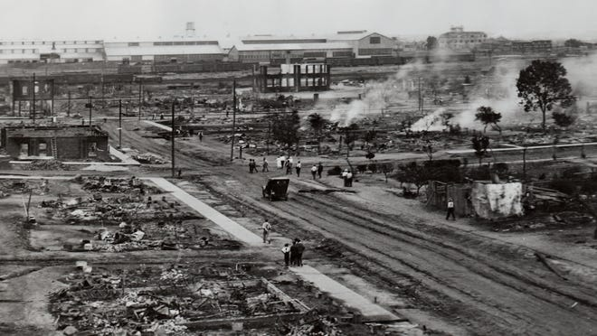 The Greenwood district, otherwise known as the Black Wall Street, destroyed and still smoking in this aerial shot taken in the aftermath of the Tulsa Race Massacre of 1921.