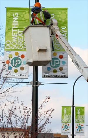 Ron Sayre, an equipment operator with the City of Akron, hangs two University Park Alliance banners on a pole on Brown Street on Jan. 5, 2011, in Akron.