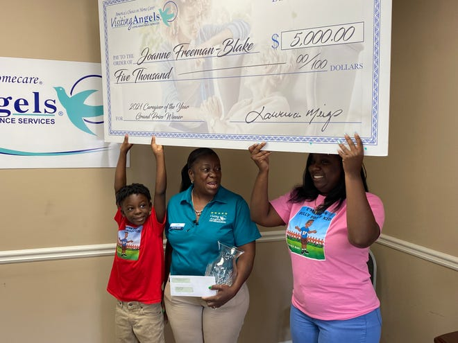 Joanne Freeman-Blake, center, received a $5,000 check after being named Visiting Angels' national Caregiver of the Year.