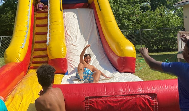 Omar Ferrietiz, 10, goes down a water slide at Ms. Myrt's House during one of the Grovetown child care center's summer camps.