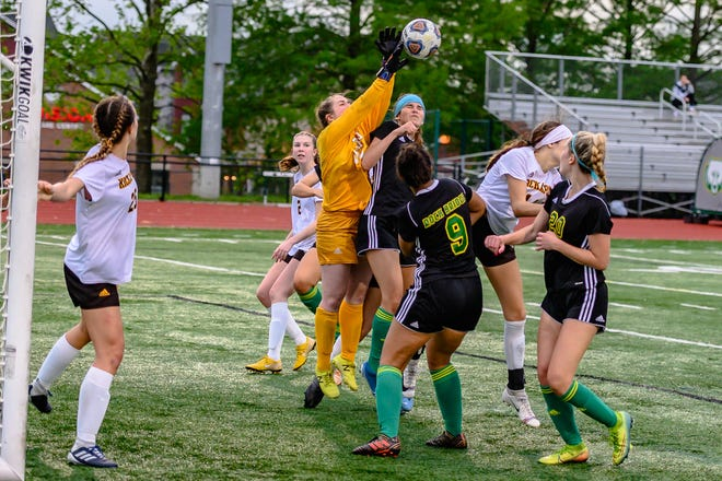 Kickapoo's Chloe Young (99) tips the ball over the head of Ella Hendershott (16) of Rock Bridge during their sectional playoff game Tuesday night.