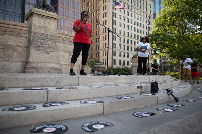 Broken records with names of police shooting victims line the steps at the Ohio Statehouse as Adrienne Hood, whose son Henry Green was killed by Columbus police in 2016, speaks during a vigil held Tuesday to mark the one-year anniversary of George Floyd's death and to encourage support for an amendment to the state constitution to remove qualified immunity for law enforcement officers.