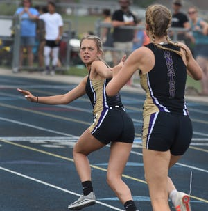 Kara Terakedis of Onsted takes the baton from Kayla Ross in the 3.200 meter relay going onto win the race in the  LCAA League meet finals Tuesday, May 25, 2021. Terakedis also won the 1,600 meter run. [TOM HAWLEY/MONROE NEWS]