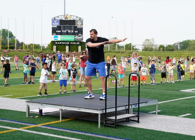 Doug Gray, president of the Gray Institute, leads approximately 400 Lincoln Elementary School students in movement exercises Tuesday at Docking Stadium at Adrian College.