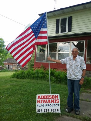 Addison resident Walt Dentel shows off his flag from the Kiwanis Club of Addison flag program. Flags are placed around the community for all major flag holidays during the spring, summer and fall.