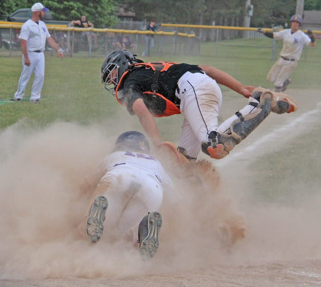 Quincy catcher Cody Neusbaum and Bronson base runner Dylan Smith engage in a play at the plate Tuesday. Smith was called safe as the ball squirted away from Neusbaum.
