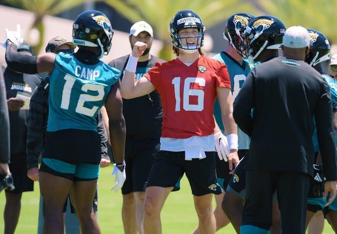 Jaguars quarterback Trevor Lawrence (16) talks with teammates during drills at rookie minicamp.