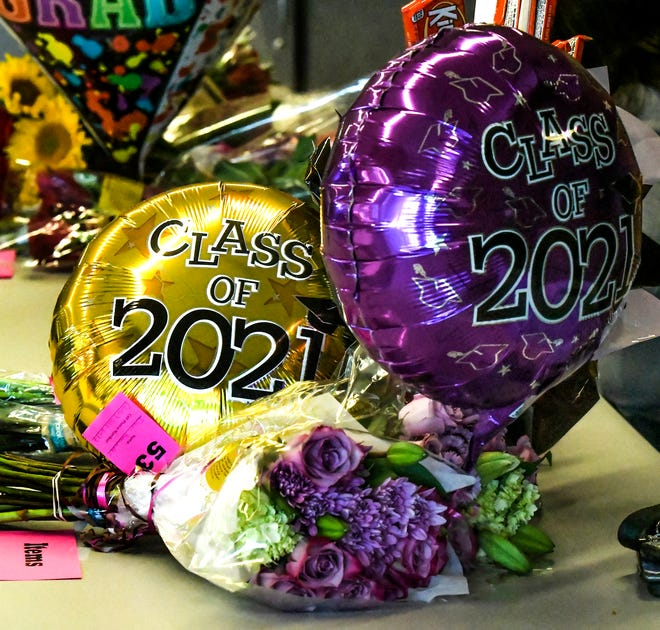 Balloons and flowers for graduates sit on tables outside the Garden City High School gym during one of the graduation ceremonies. USD 457's Alternate Education Center and Virtual Academy held its graduation on Saturday.