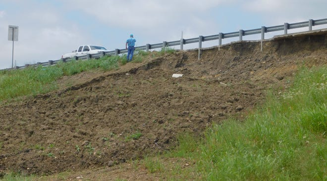 A contractor assesses damage from a mud flow along U.S. 82 in Sherman Wednesday. The mud landslide between Loy Lake Road and Texoma Parkway is one of several mud landslide points along the highway that have occurred following prolonged rain and ground saturation in recent weeks. Once the ground dries, Texas Department of Transportation crews will use heavy machinery to reposition the slope and drive pilings into the ground to secure it, officials said.
