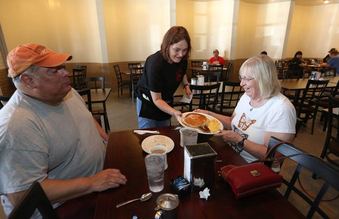 Cyndy Landon, right, receives her breakfast from waitress Diane Williams Wednesday morning at Alyce's Restaurant on the main floor of the Plaza Towers Community apartment complex, with Charlie Navarro, left.
