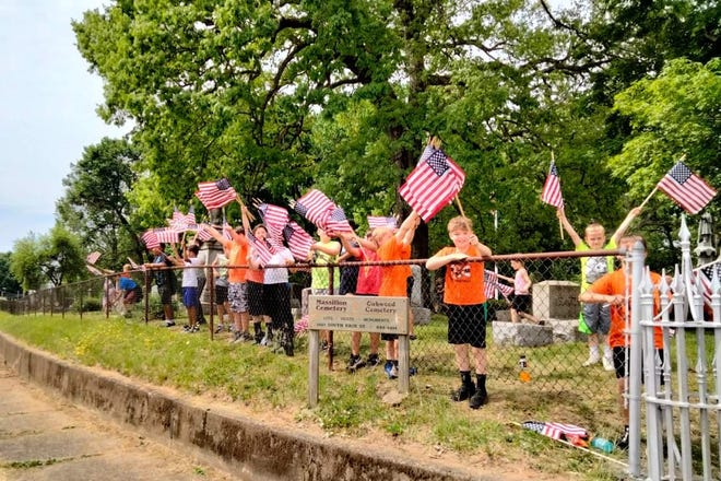More than 50 members of the Ohio Tigers Premier Football Academy took part in a community flag posting event Saturday at St. Joseph Cemetery and the Massillon Cemetery. The youths also cleaned gravesites of U.S. military veterans.