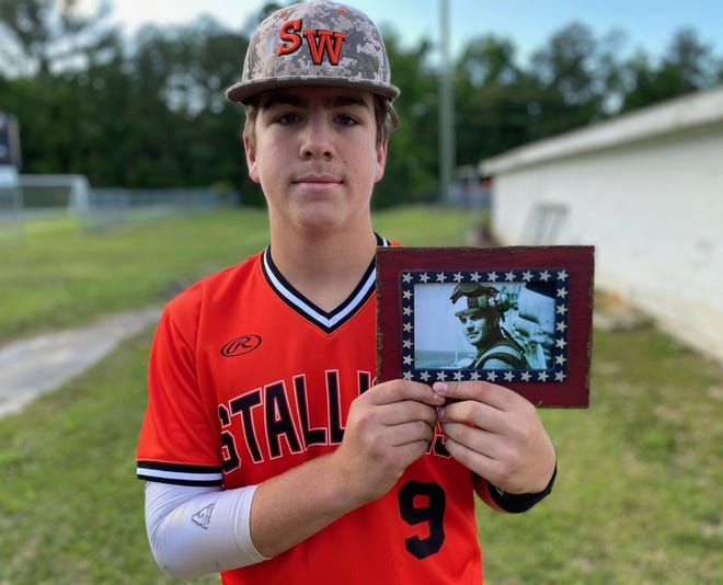 Southwest freshman baseball player Carter Dudley holds up a photo of his late father, Thomas, who passed away 10 years ago while serving in Afghanistan. [Chris Miller / The Daily News]