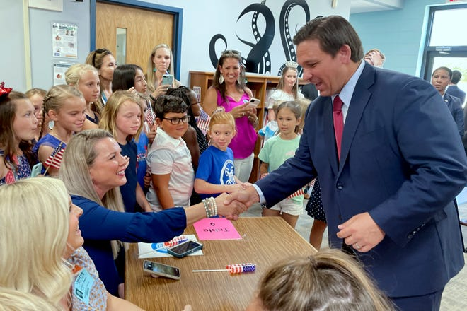 Gov. Ron DeSantis shakes hands with teacher Jenna Jannazo during a recent visit to Destin Elementary School, where he announced that Florida teachers would receive a $1,000 bonus from the state.