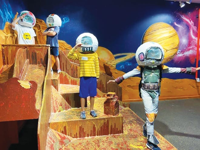 """Children wear the papier-mâché astronaut helmets they created in the """"Out of This World"""" summer camp last year as they play in the Children's Museum's Mars Rocket Room."""