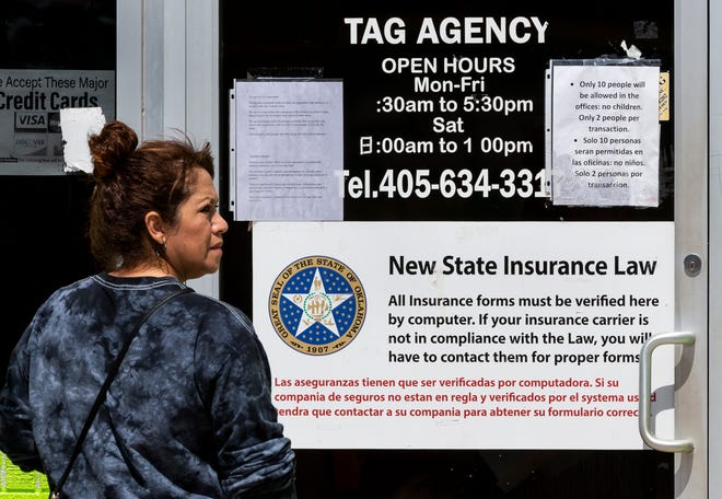 A customer stands outside the 29th St. Tag Agency as she waits in line for service in Oklahoma City, Okla. on Tuesday, March 31, 2020.