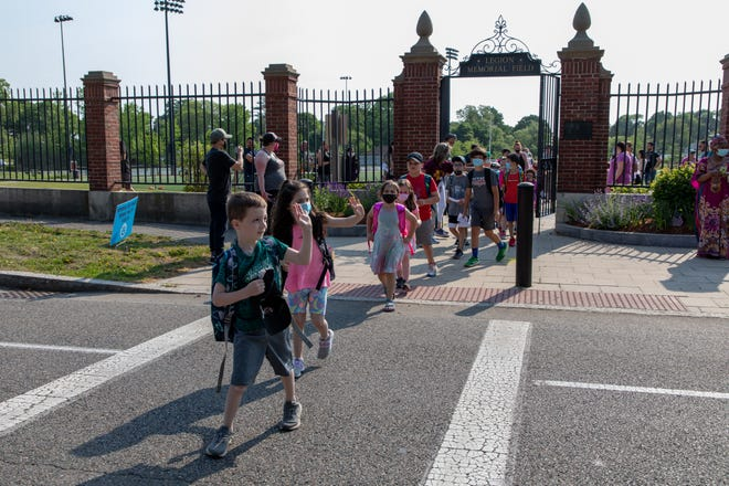 Paul Whittle, a kindergarten student at Academy Avenue Elementary School, waves to cars while crossing the street as he makes his way to school from Legion Memorial Field on Wednesday, May 26, 2021. Mike Mejia/For The Patriot Ledger