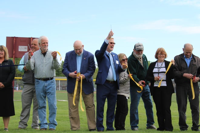 Mike Cain (center), Boyne City's city manager, celebrates Wednesday after cutting the ribbon of a new radio tower in Charlevoix Township. The completion of the tower brings a close to a multi-year effort to upgrade the Charlevoix, Cheboygan and Emmet County emergency response radio system.