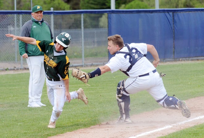 Petoskey's Kolton Horn (right) tags out a Midland Dow player caught in a rundown during the opener Wednesday.