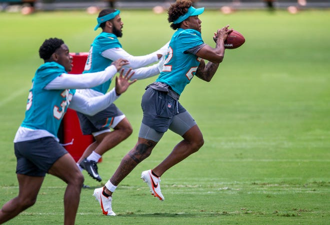 Dolphins safety Jevon Holland makes a catch during OTAs.