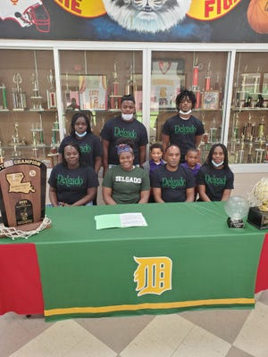 East Iberville senior Dedreka Wilson signed a basketball scholarship with Delgado Community College last week. She is seen here with her family and girls head basketball coach Mark Temple, who led the Lady Tigers to the 2021 Louisiana High School Athletic Association Class 1A state championship.