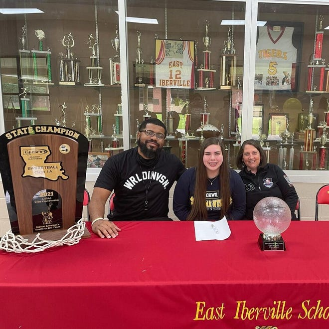 East Iberville graduate Carson Dean recently signed a scholarship to play basketball for University of Oklahoma Wesley. She is pictured with head basketball coach Mark Temple and her mother, Stacey Dean.