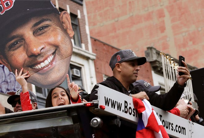 Boston Red Sox manager Alex Cora takes a photo as his daughter Camila, left, holds a cutout photo of him during a parade to celebrate the team's World Series championship over the Los Angeles Dodgers, Wednesday, Oct. 31, 2018, in Boston. (AP Photo/Charles Krupa)