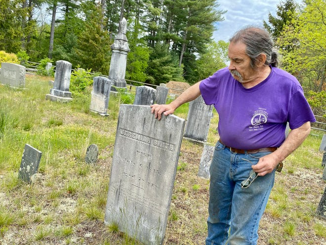 Terry Bates stands beside the gravestone of his property's original homesteader, Jeremiah Smith.