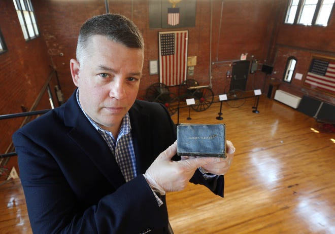 Patrick Donovan, curator of the Varnum Memorial Armory Museum in East Greenwich, will be master of ceremonies for the return of the Memorial Day parade in East Greenwich on Monday morning. Here, he is holding the Bible of Alfred G. Gardner, who was killed in action on the third day of the Battle of Gettysburg, July 3, 1863.