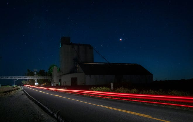 """A rare supermoon coincides with a total eclipse, seen in the skies above a grain silo on Staten Island Road near Walnut Grove in the Delta. Also known as a blood moon for the color it often turns during a total eclipse, a supermoon occurs when a full moon is closer than usual in its elliptical orbit, making it appear slightly larger. May's full moon is also called a """"Flower Moon"""" by the Old Farmer's Almanac, referring to the flowers that bloom in May."""