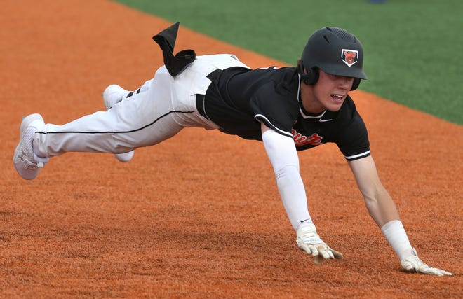 Connor Ashby of Hoover dives into third base during their Division I district semifinal against Green at Hudson on Tuesday, May 25, 2021. The play produced Hoover's first run of the game.