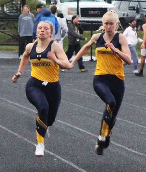 Mooresville juniors Madelyn Denny (left) and Alysha Bradford run shoulder to shoulder during the Mid-State Conference Championships. Denny and Bradford both qualified for the state finals, with Denny competing in the 100-meter dash after finishing second in regionals. Bradford will compete in the 200-meter race after finishing third in the regional meet. (Steve Page / Correspondent)
