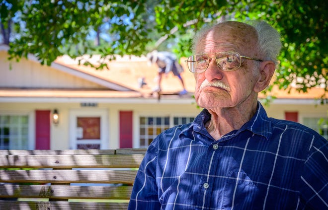 Paul Bass, 90, sits under a tree in the front yard of his home in Flagler Estates as workers from Reiter Roofing replace the roof of his home on Wednesday.